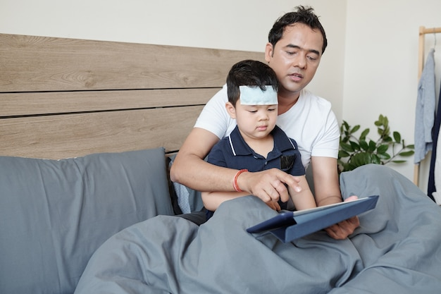 Father sitting in bed with his little sick son trying to entertain him with game on tablet computer and distract from fever