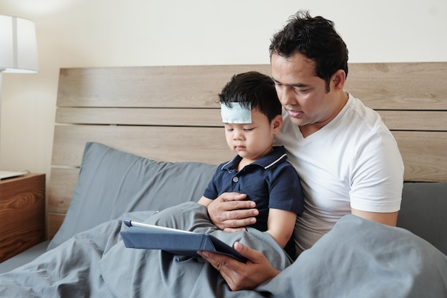Father sitting in bed with his sick little son and reading him e-book or showing cartoon