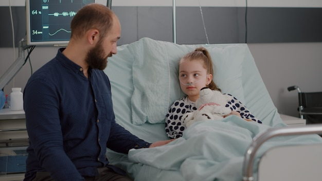 Father sitting beside sick daughter discussing sickness therapy explaining medication treatment during disease examination in hospital ward. little kid lying in bed after suffering medical surgery