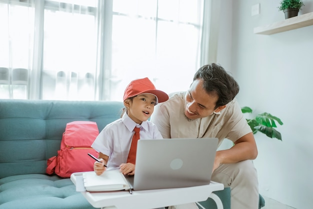 Father sitting next to her daugther during her online class conference with school at home