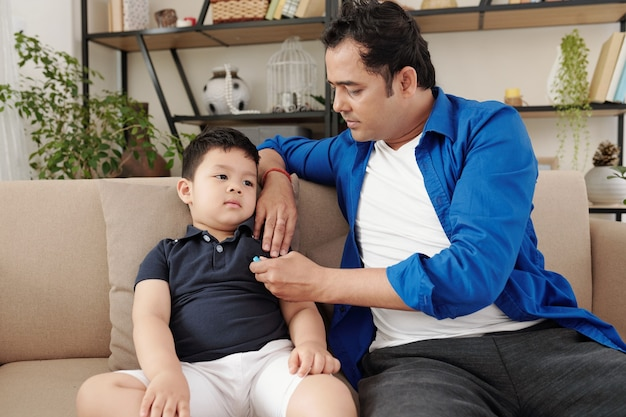 Father sitting on sofa and measuring body temperature of his little son feeling unwell