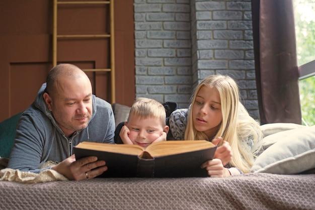 Отец, сын и дочь читают книгу в постели