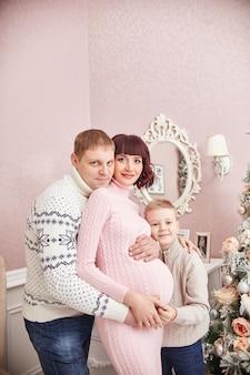 父、息子、妊娠中の母親が屋内でポーズ