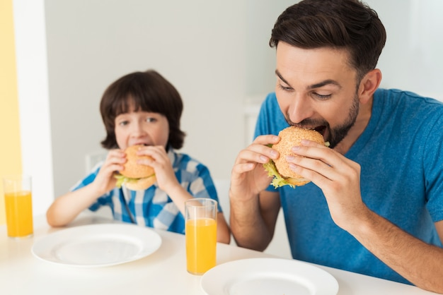 Father and son are eating a hamburger with juice.