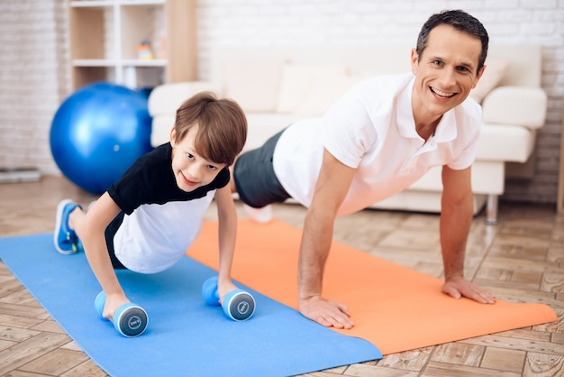 Father and son are engaged in fitness together with fitball.