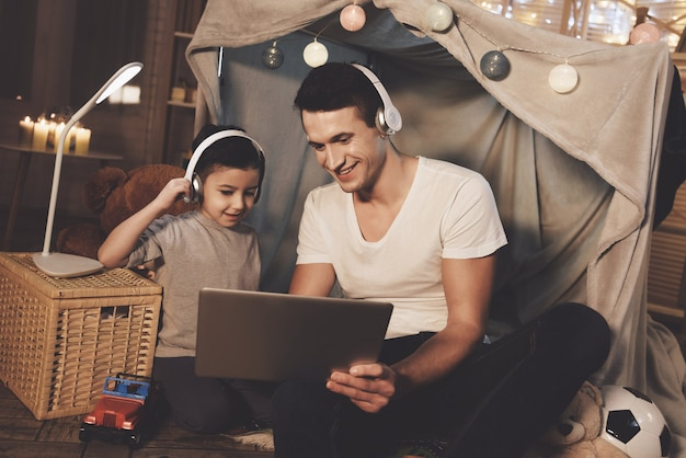 Father and son are listening to music on laptop at night.