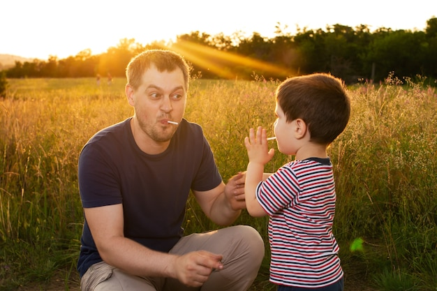 Father and son are playing outdoors in a field at sunset.