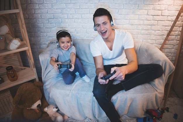 Father and son are playing video games on tv at night