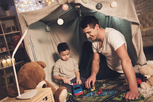 Father and son are playing with cars on carpet road