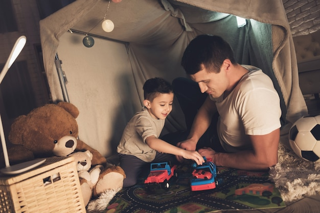 Father and son are playing with cars at night.