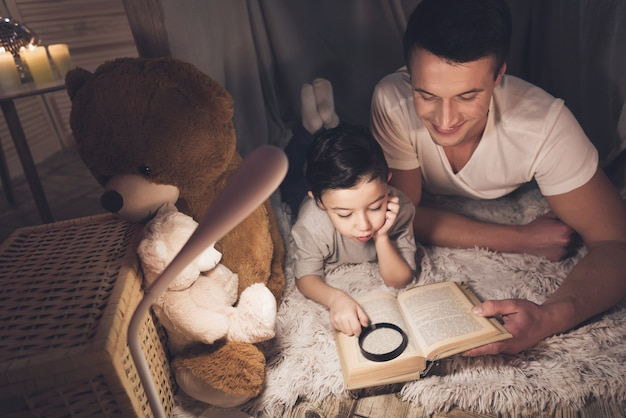 Father and son are reading book at night at home.