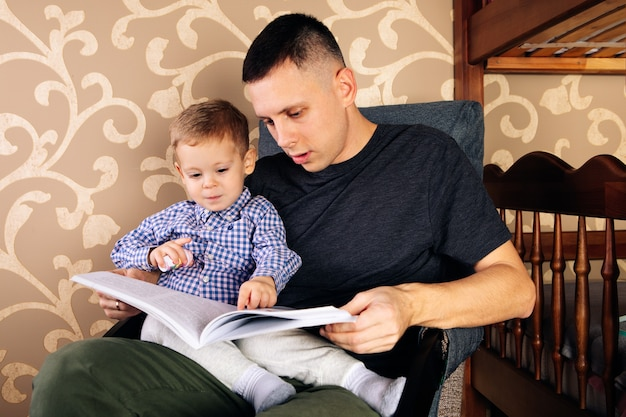 Father and son are reading a book and smiling while spending time together at home