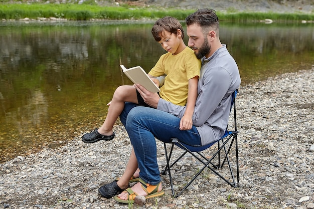 Father and son are sitting in folding chair near river, parent teaches child to read.