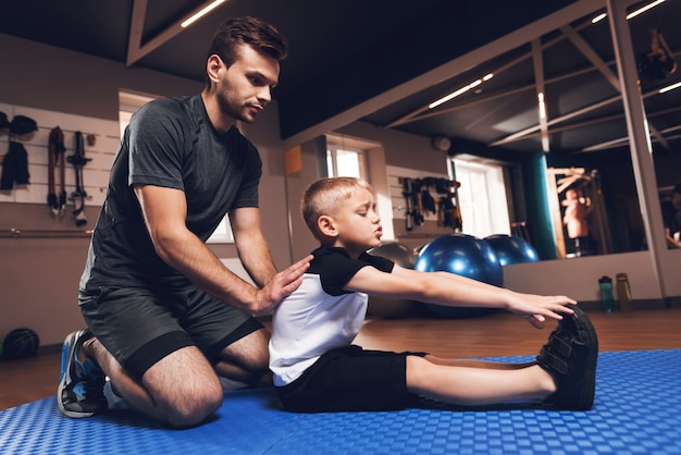 Father and son are stretching each other in gym.