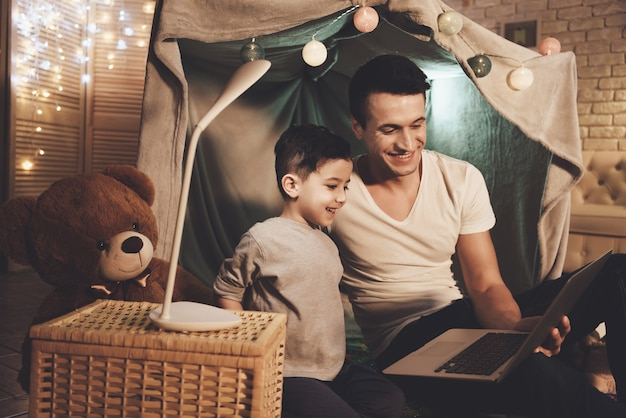Father and son are watching movie on laptop at night at home