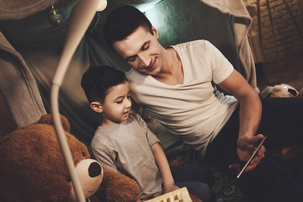 Father and son are watching movie on tablet at night at home