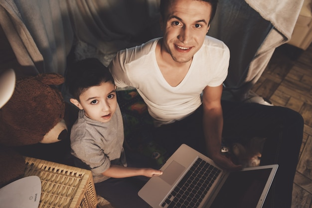 Father and son are watching video on laptop at night at home