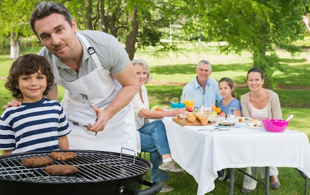 Father and son at barbecue grill with family having lunch in park