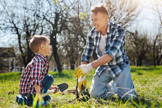 Father and son both wearing plaid shorts smiling while setting a new tree in a family garden