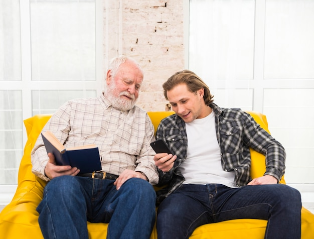 Father and son browsing information in cell phone