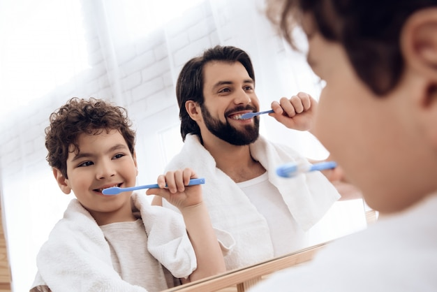 Father and son brush teeth with toothbrush.