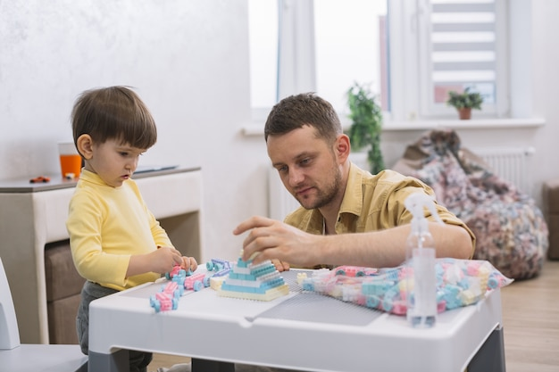Father and son building toys from lego pieces