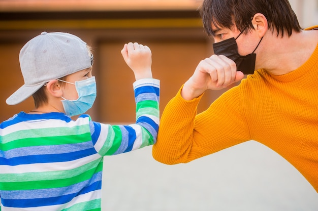 Father and son bump elbows outdoors. coronavirus quarantine. social distancing concept. coronavirus outbreak. protective measures. father puts her son a face protective mask outdoors.