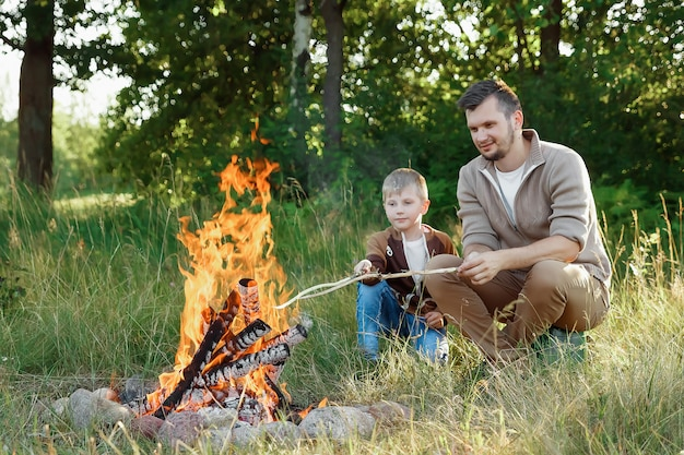 Father and son by the fire on green nature.