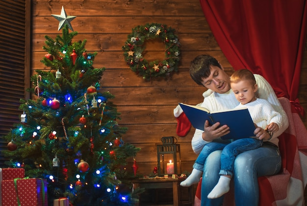Father and son celebrate christmas in a decorated house with a christmas tree and read the book