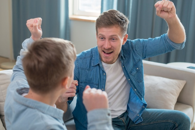 Father and son cheering in the living room