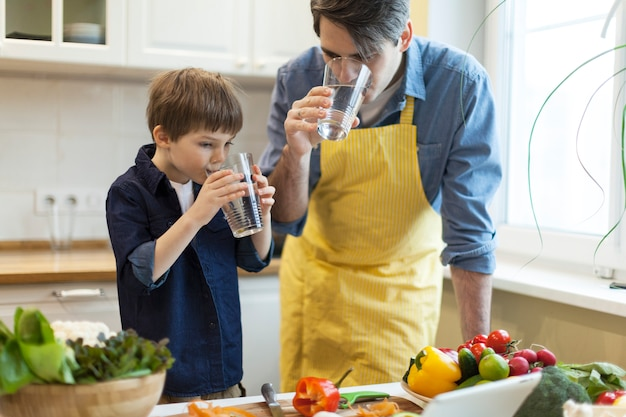 Father and son cooking in kitchen