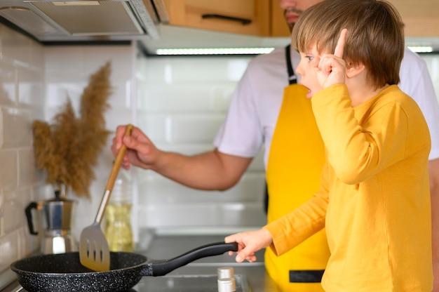 Padre e figlio che cucinano in una padella