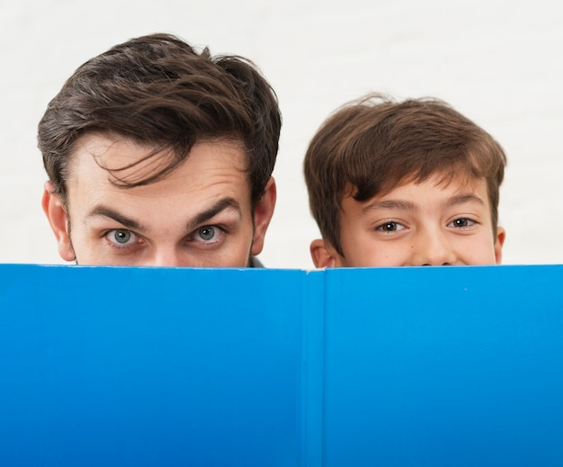 Father and son covering their faces with a blue book Free Photo