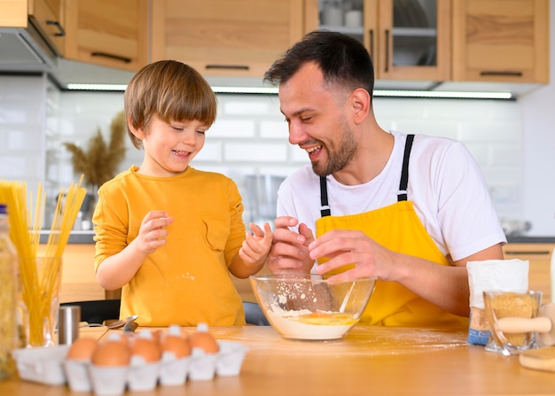 Father and son cracking eggs for cooking