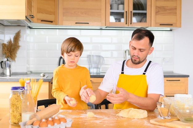 Father and son creating balls of dough front view