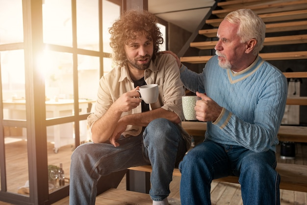 Father and son drink a coffee together. concept of family relationship