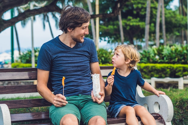 Father and son eat fried sweet potatoes in the park.