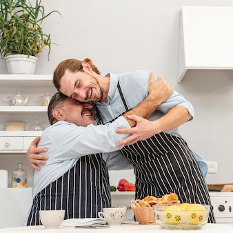 Father and son embracing in kitchen