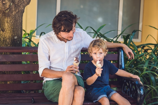 Father and son enjoying ice cream outside in a park.