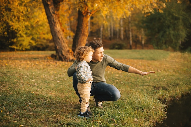 Father and son exploring nature outdoor in park at sunset