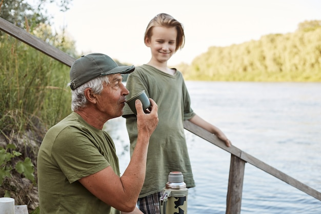 Father and son fishing at bank of river or lake, senior man drinking tea from thermos, family posing on wooden stairs leading to water, rest on beautiful nature.