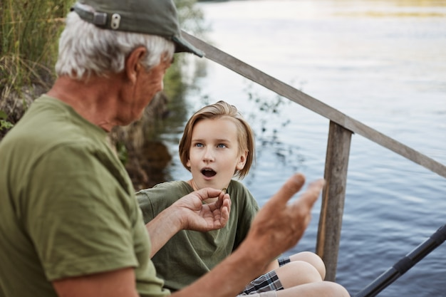 Father and son fishing near river, dad telling about last fishing, showing size of catching fish, son listening with astonished facial expression and opened mouth.
