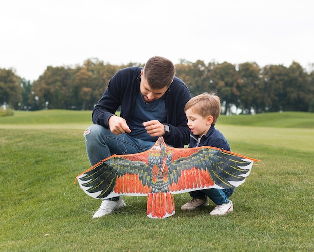 Father and son fixing a kite