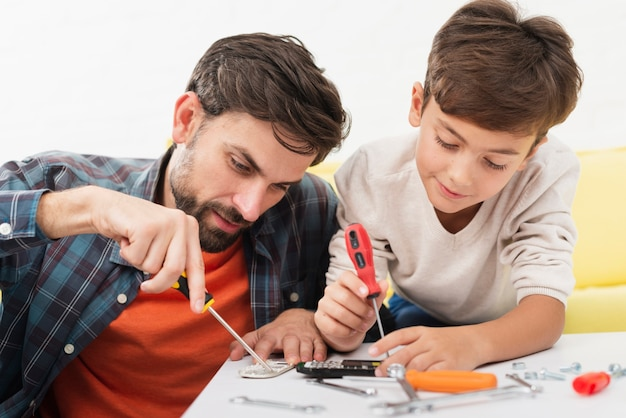 Father and son fixing toy cars
