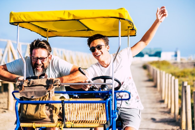 Father and son friends have fun together laughing a lot on a vehicle bike