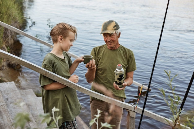 Father and son go fishing, drinking tea from thermos while standing wooden stairs leading to water, family having rest on beautiful nature, enjoying being outdoors in open air.
