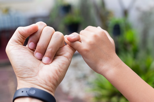 Father and son hands hooking each other on little finger making promise together