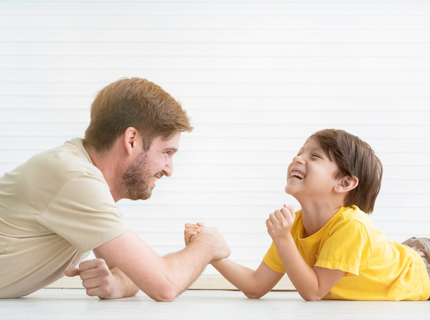 Father and son having arm-wrestling competition at home.