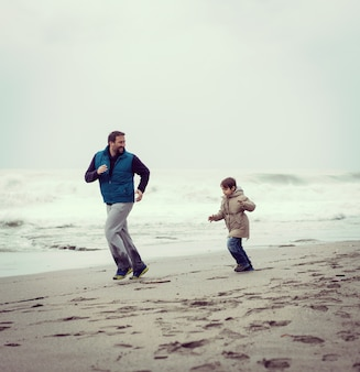 Father and son having fun on winter beach