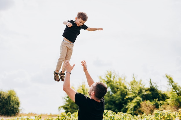 Father and son having a funny time outdoor. dad throws son up in the air